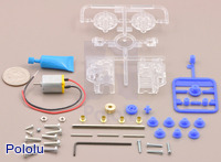 Parts included with the Tamiya 70189 mini motor low-speed gearbox (4-speed) kit with quarter for size reference.