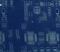 Close-up of a mylar solder paste stencil (the mylar is not stretched flat, making the apertures look distorted).